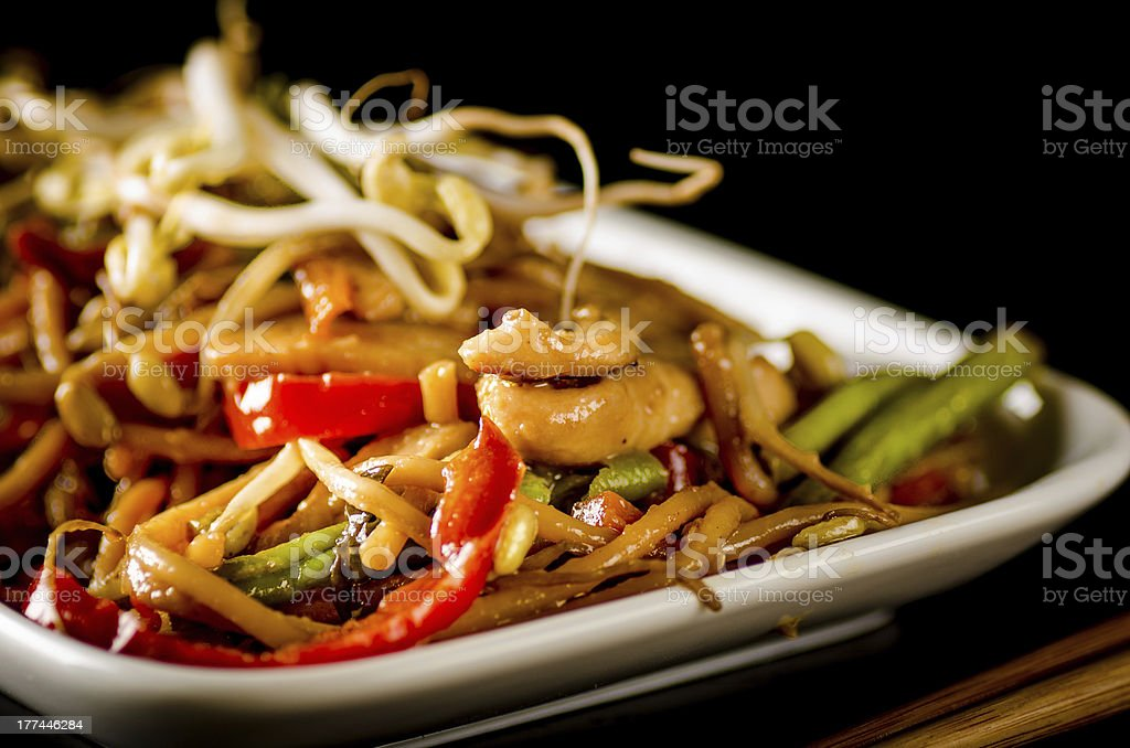 Stir-fried chinese noodles with chicken, vegetables and beansprouts on black royalty-free stock photo