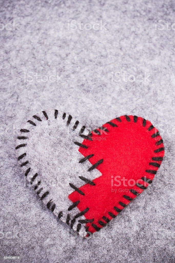 stitched broken felt heart on a on a gray background stock photo