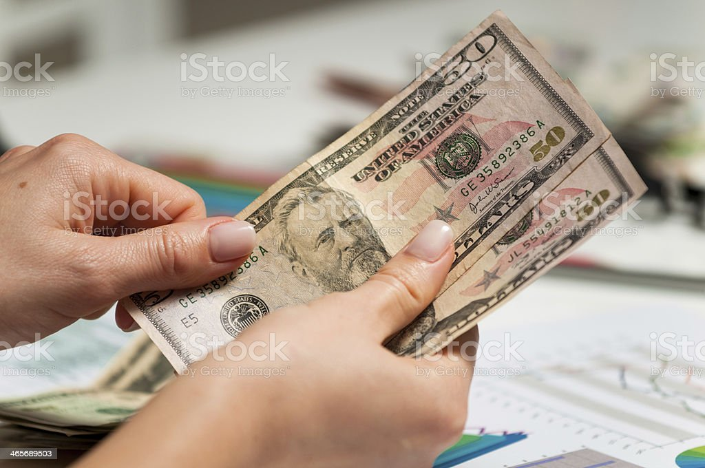 Stock broker counting profit after trading with emerging markets shares stock photo
