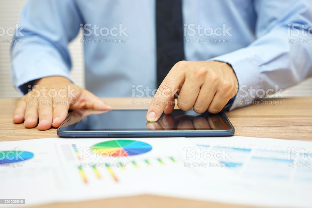 Stock broker is researching stock market on computer tablet stock photo
