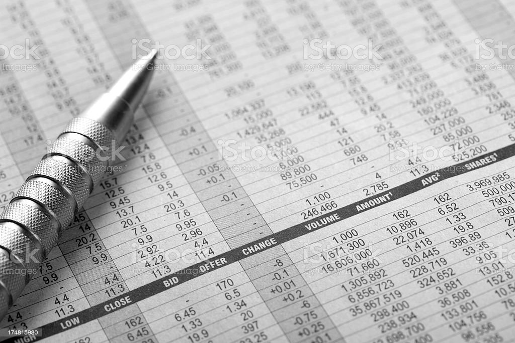 Stock market analysis with pen on newspaper stock photo