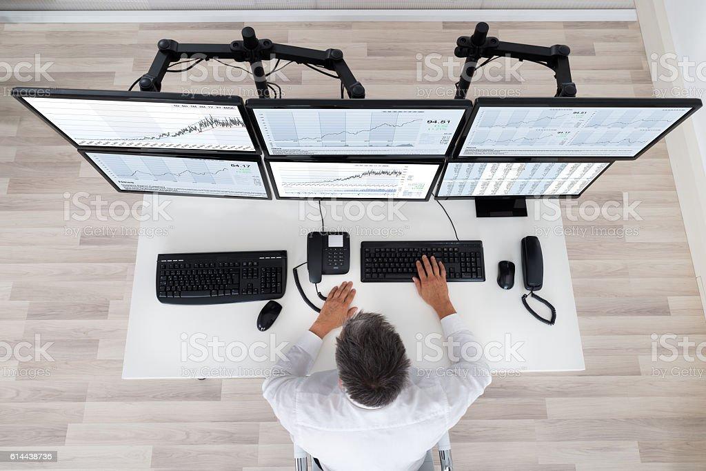 Stock Market Broker Looking At Graphs At Desk stock photo