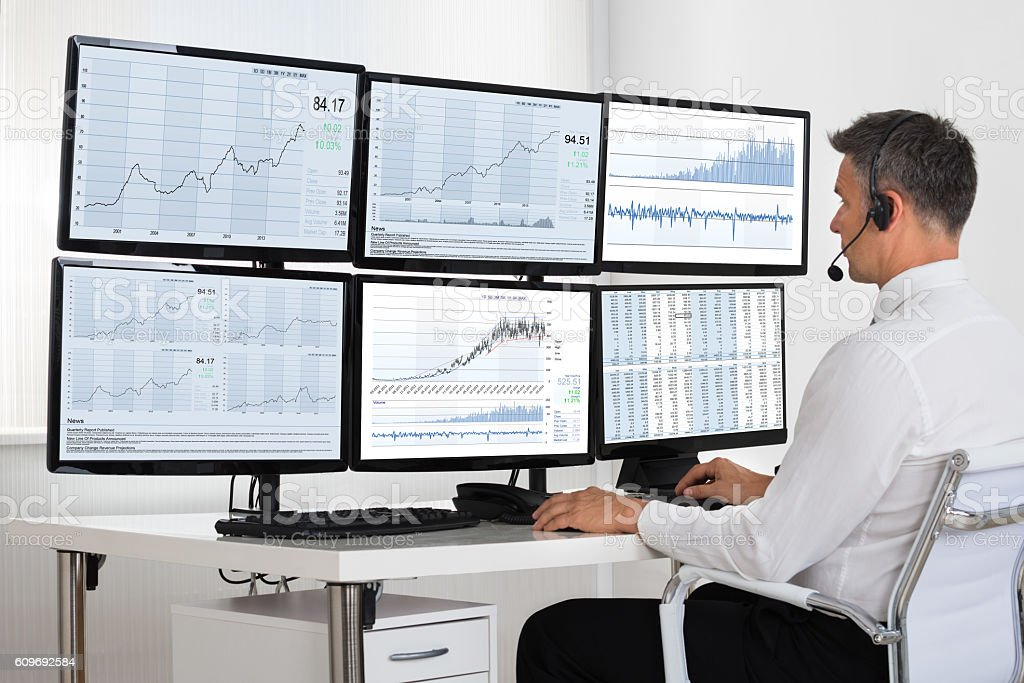 Stock Market Broker Looking At Graphs On Multiple Screens stock photo