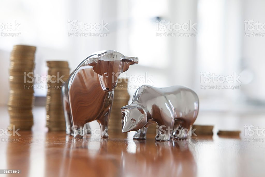 Stock market, bull and bear, figurines, stack of coins stock photo