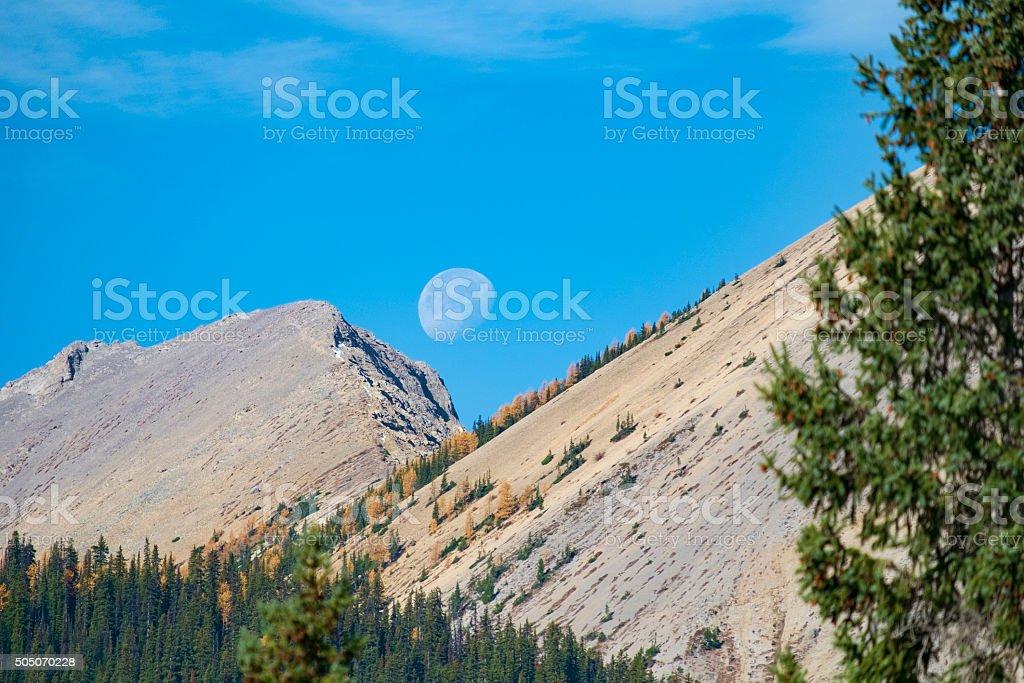 Stock Photo Of Partial Moon Over Rocky Mountains stock photo