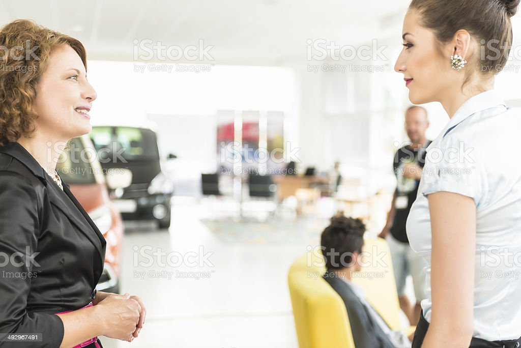 Stock photo of two women in a car dealership showroom. royalty-free stock photo