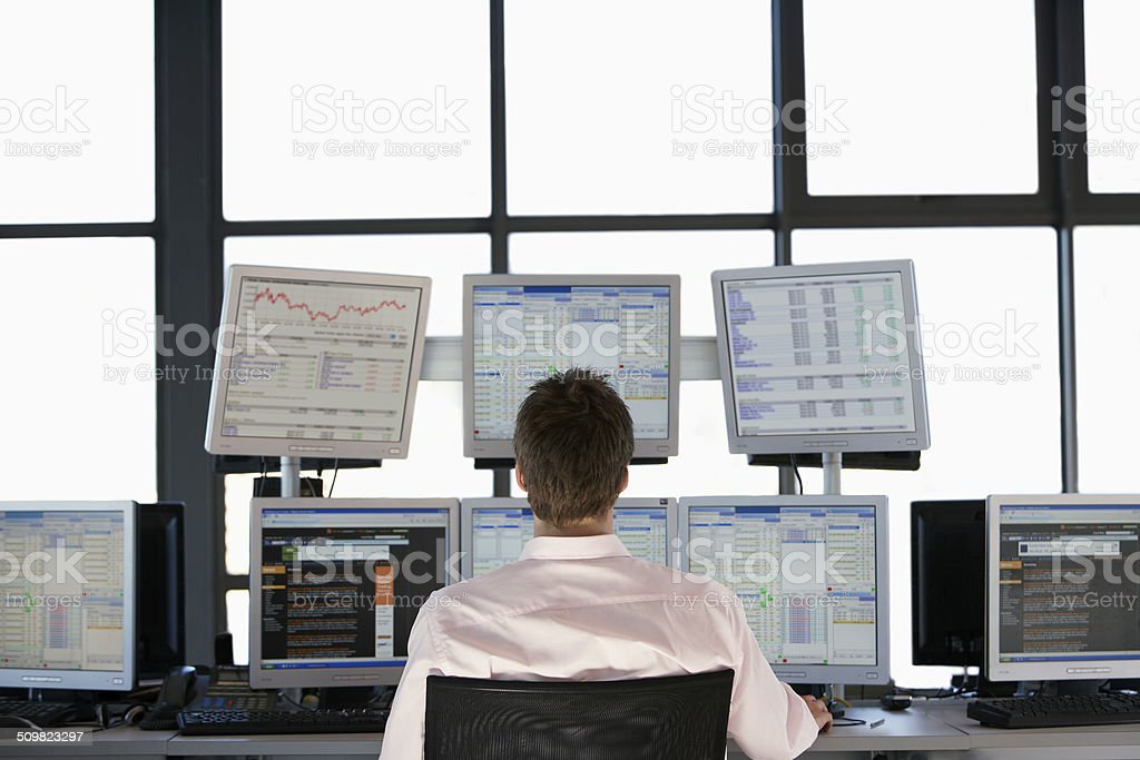 Stock Trader Looking At Multiple Computer Screens stock photo