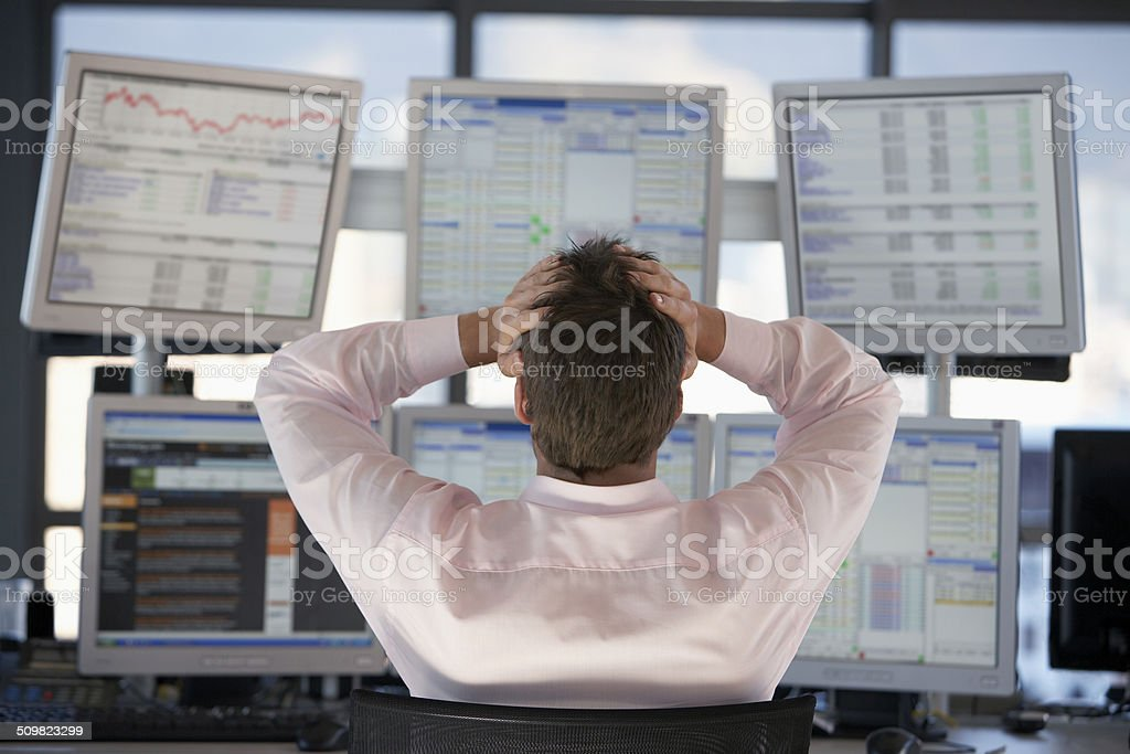 Stock Trader Watching Computer Screens With Hands On Head stock photo
