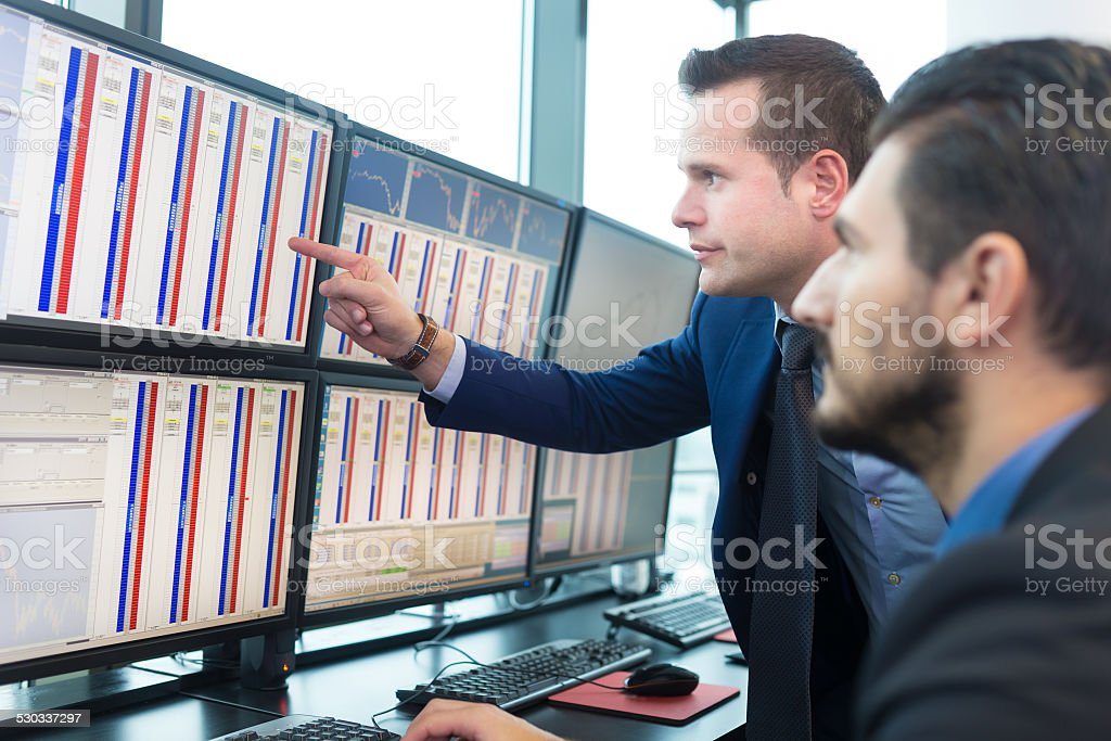 Stock traders looking at computer screens. stock photo