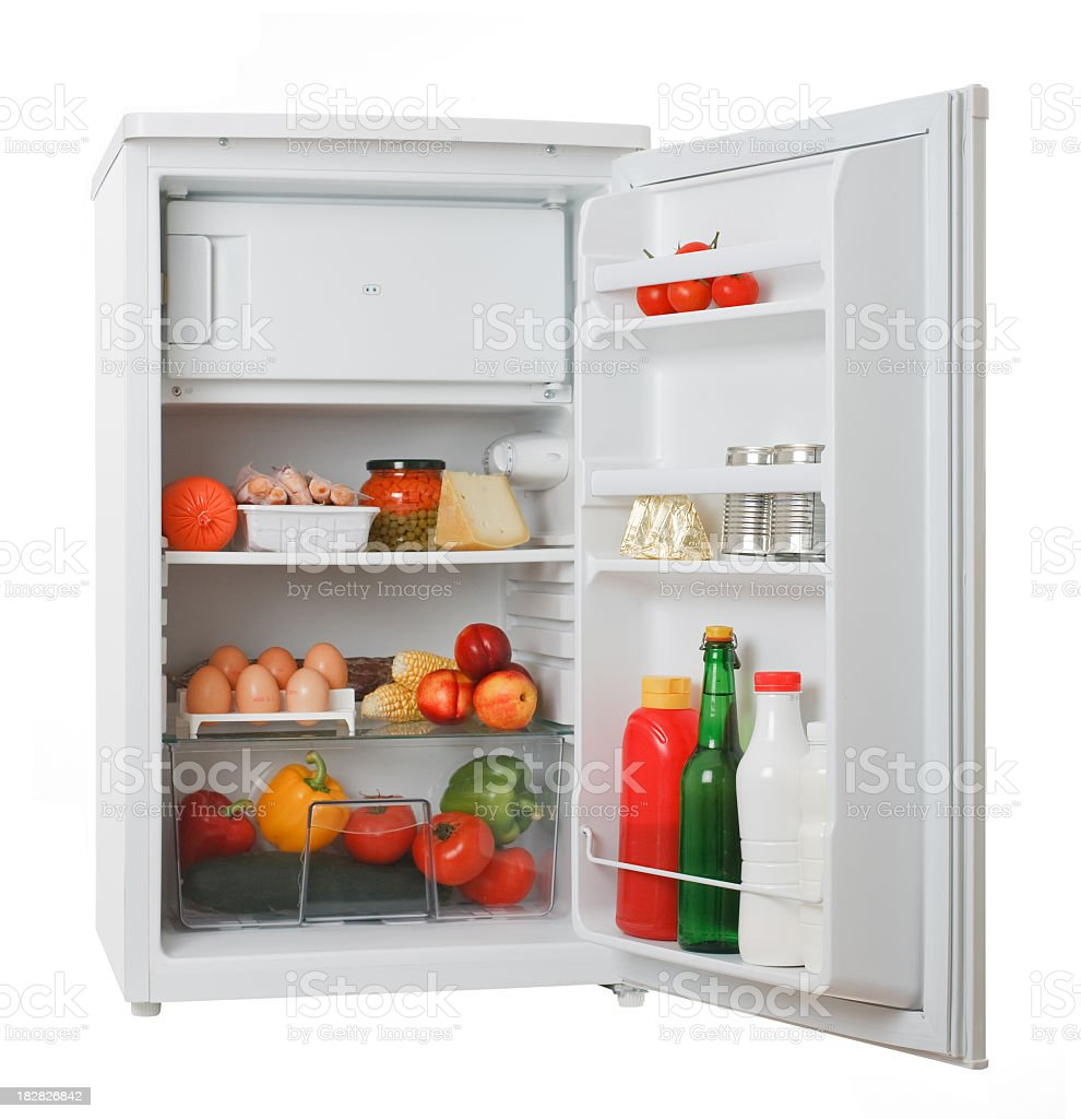 Stocked white mini fridge with produce and eggs stock photo