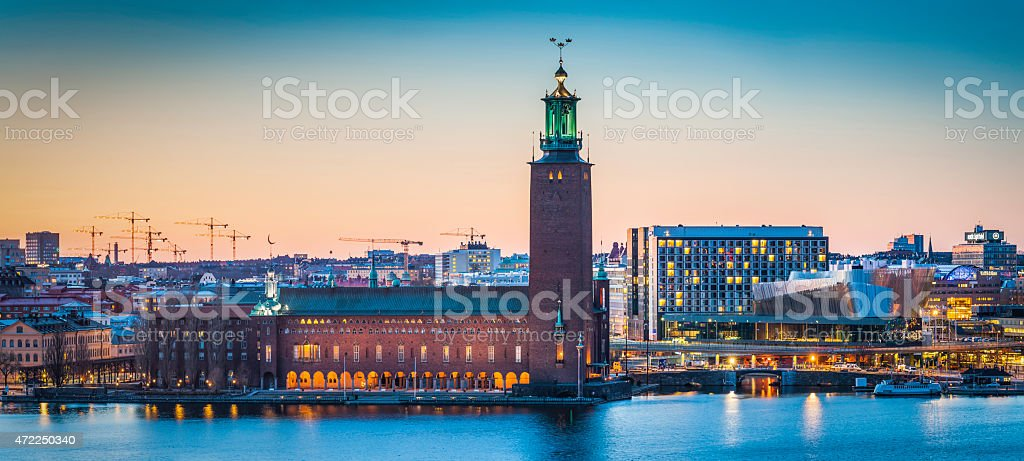 Stockholm City Hall Stadshus Riddarfjarden waterfront panorama illuminated sunset Sweden stock photo