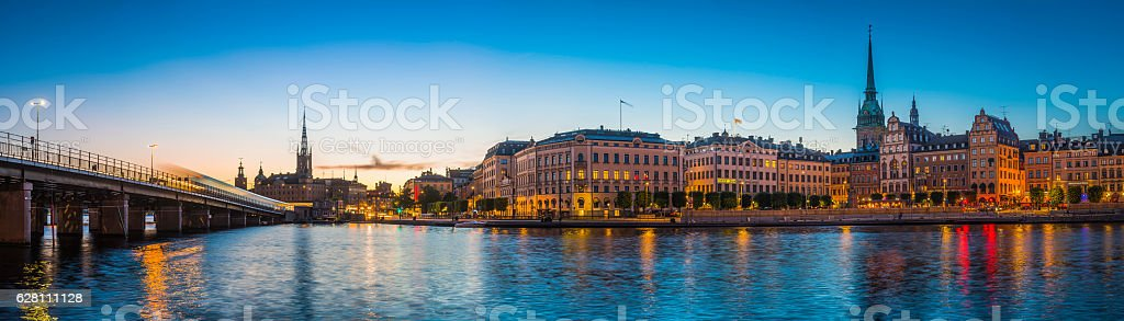 Stockholm spires and waterfront restaurants Gamla Stan illuminated sunset Sweden stock photo