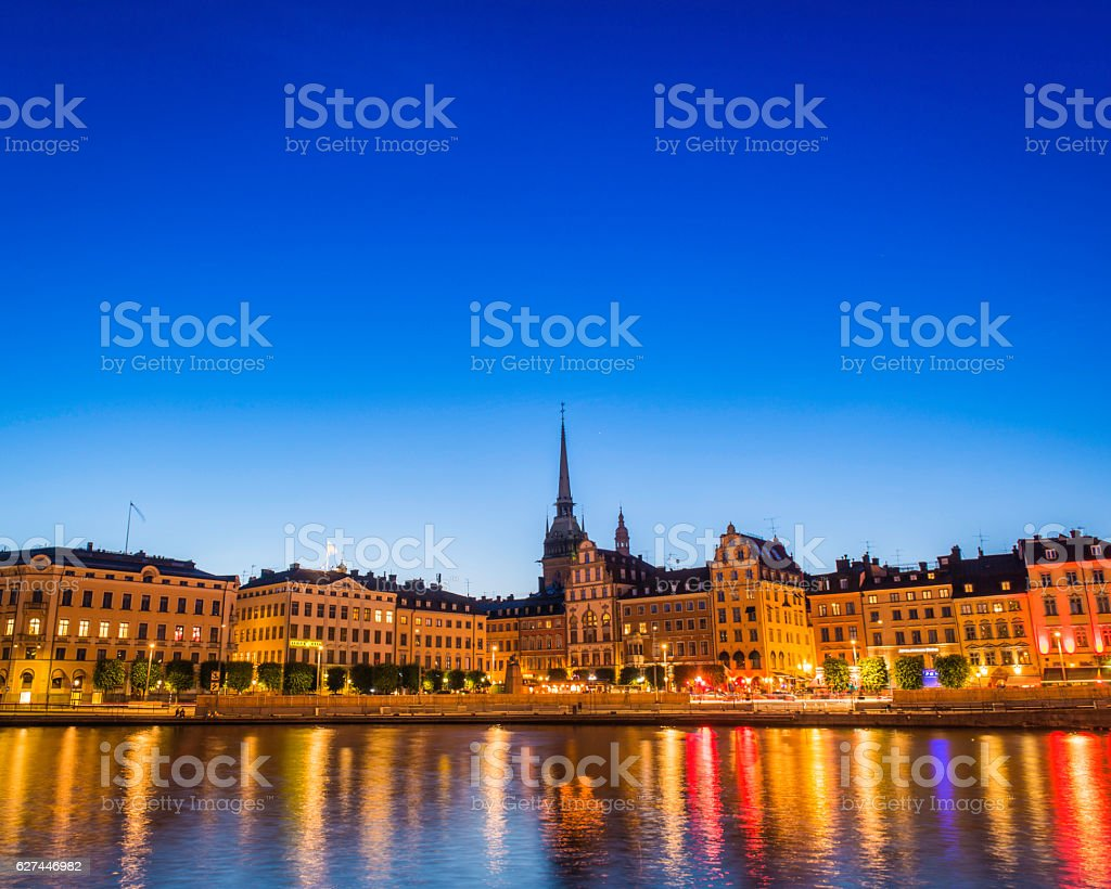Stockholm warmly illuminated restaurants townhouses spires Gamla Stan waterfront Sweden stock photo