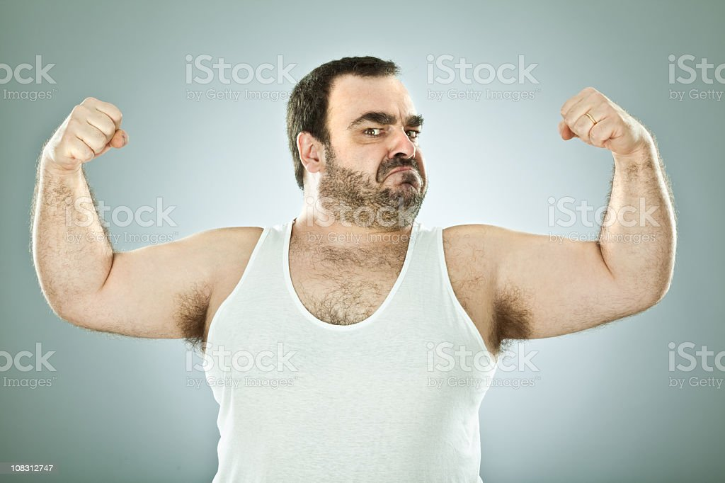 Stocky, hairy man flexing his arm muscles stock photo