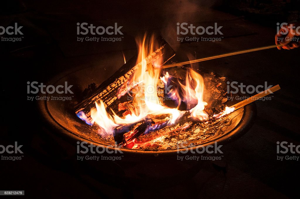 Stoking Logs On A Flaming Fire stock photo
