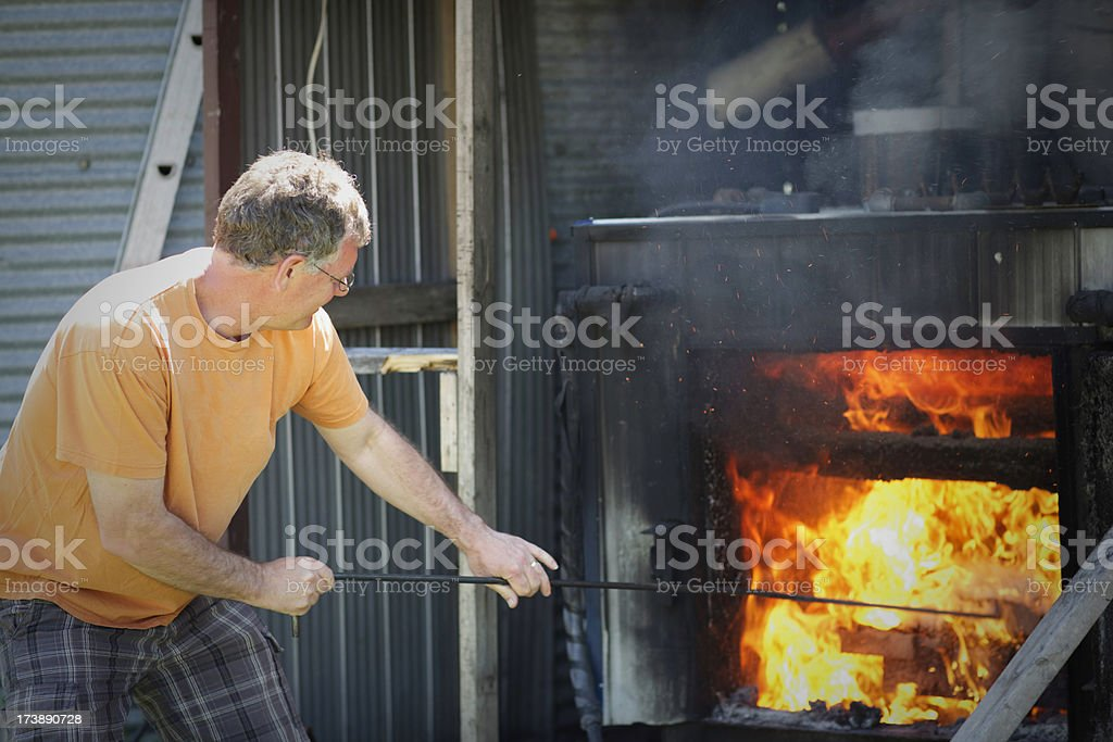 Stoking the fire furnace stock photo