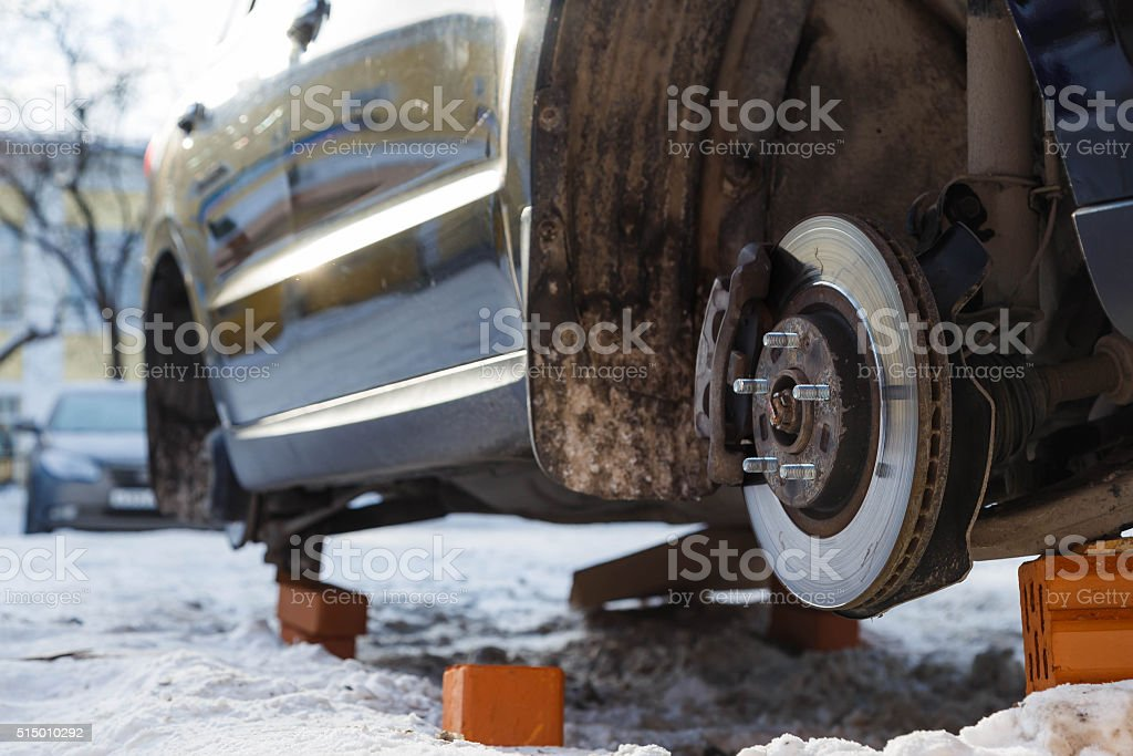stolen car without wheels winter Russian car park bottom view stock photo