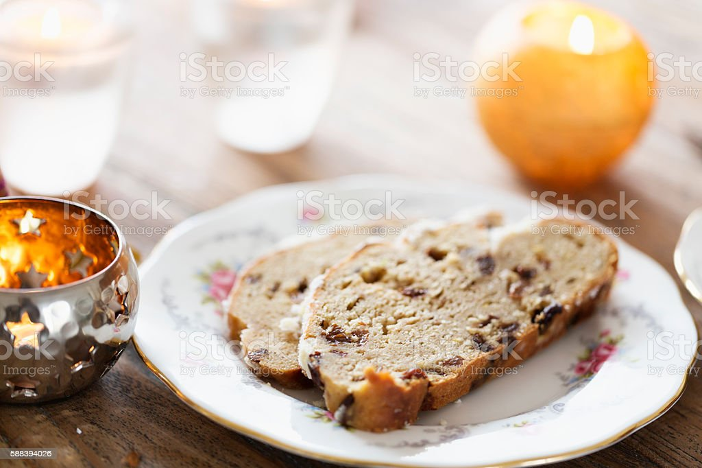 stollen and candles on table with christmas decoration stock photo
