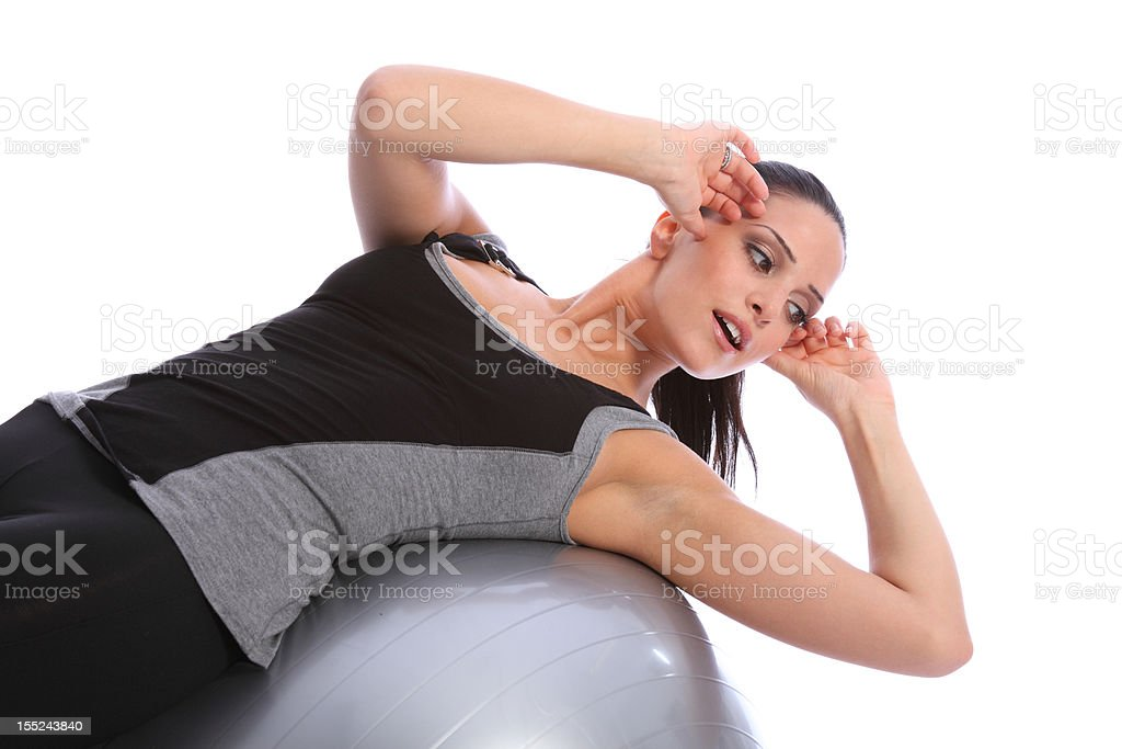 Stomach crunches by fit woman on exercise ball royalty-free stock photo
