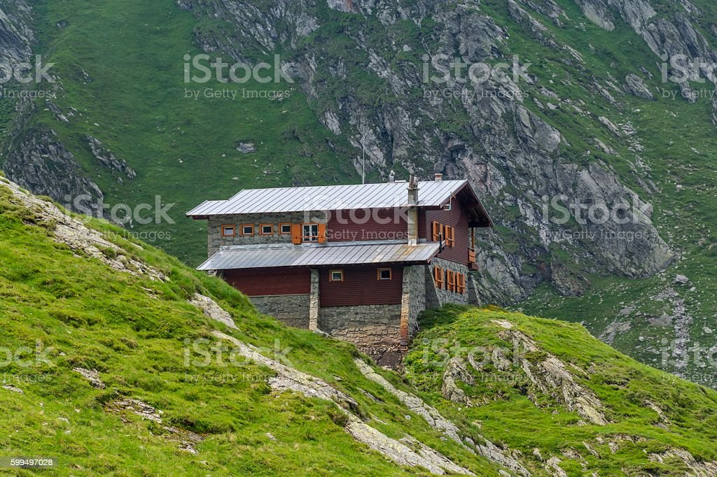 Stone and wood chalet on the mountain range stock photo
