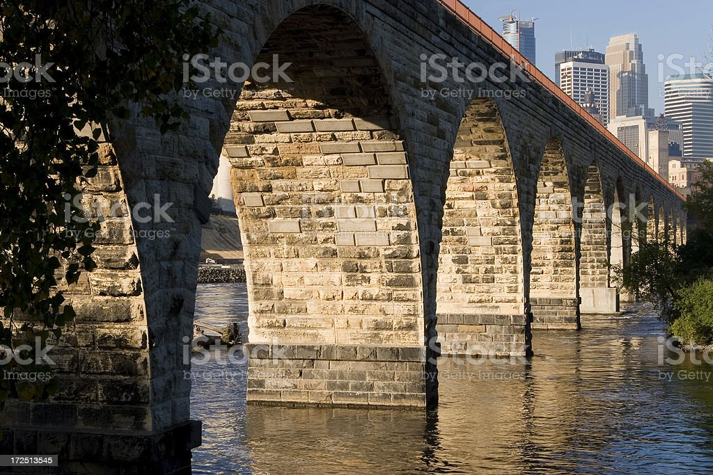 Stone arch bridge over Mississippi river and Minneapolis skyline. stock photo