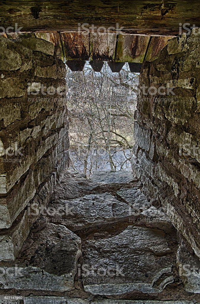 Stone arrowslit in the strengthened fortress wall stock photo