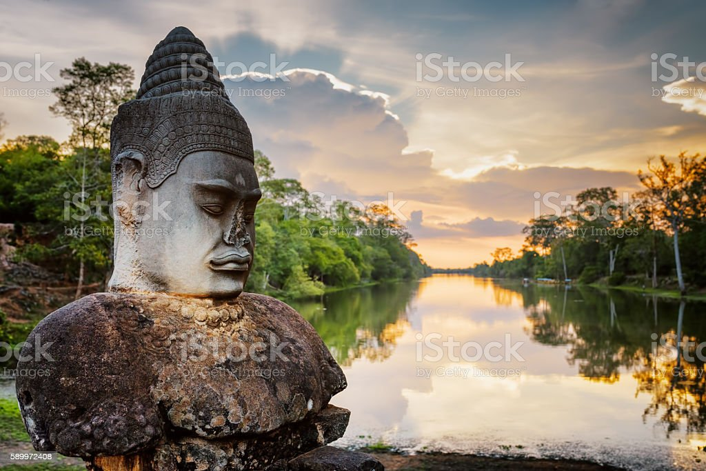 Stone Asura and sunset over moat surrounding Angkor in Cambodia stock photo