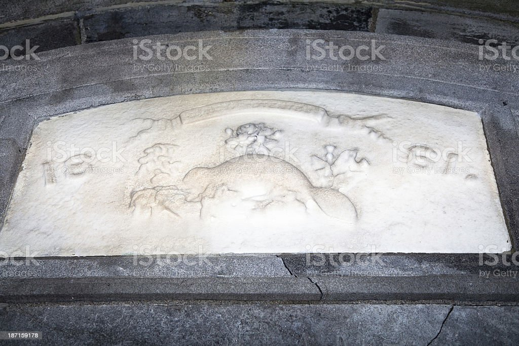 Stone beaver carved in relief above a mausoleum door stock photo
