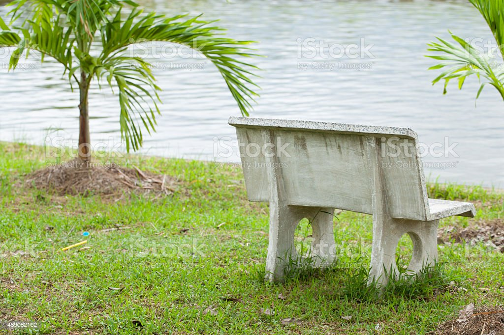 Stone bench in the grass stock photo