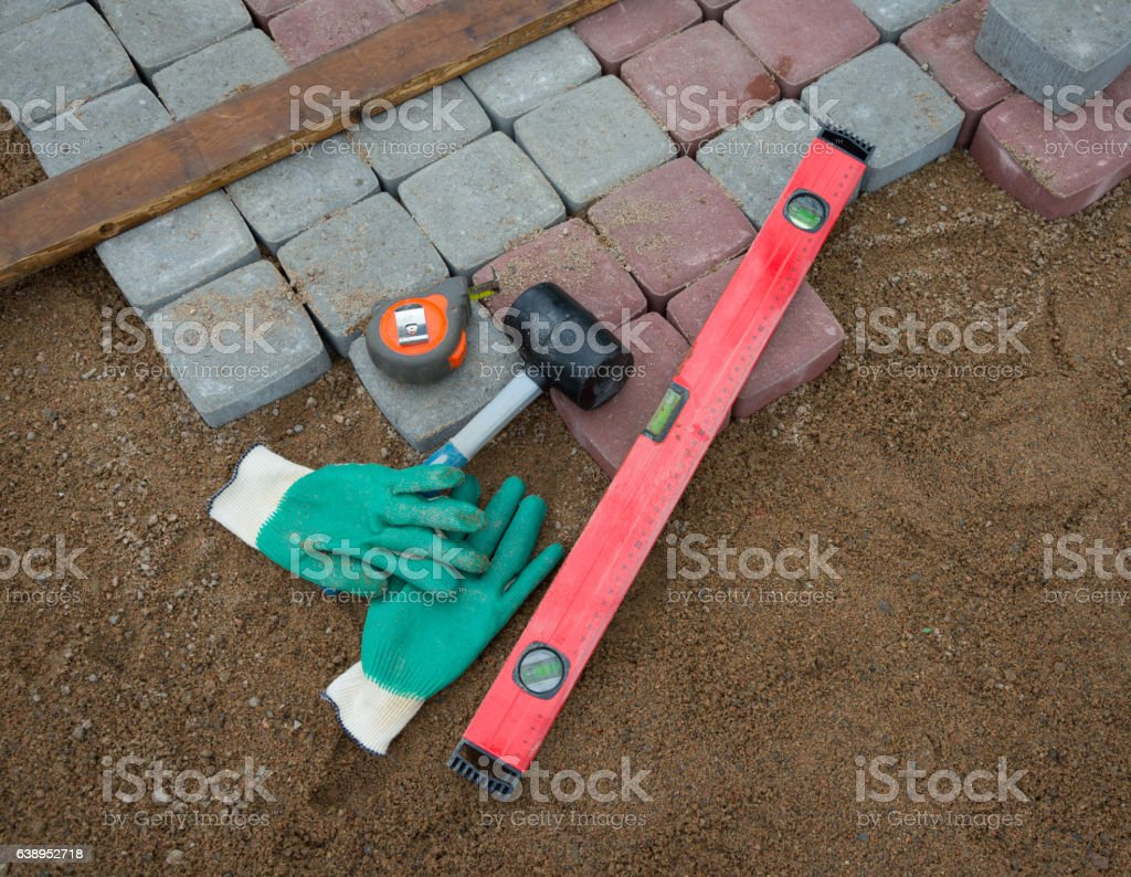 stone blocks rubber hammer level gloves and tape measure stock photo