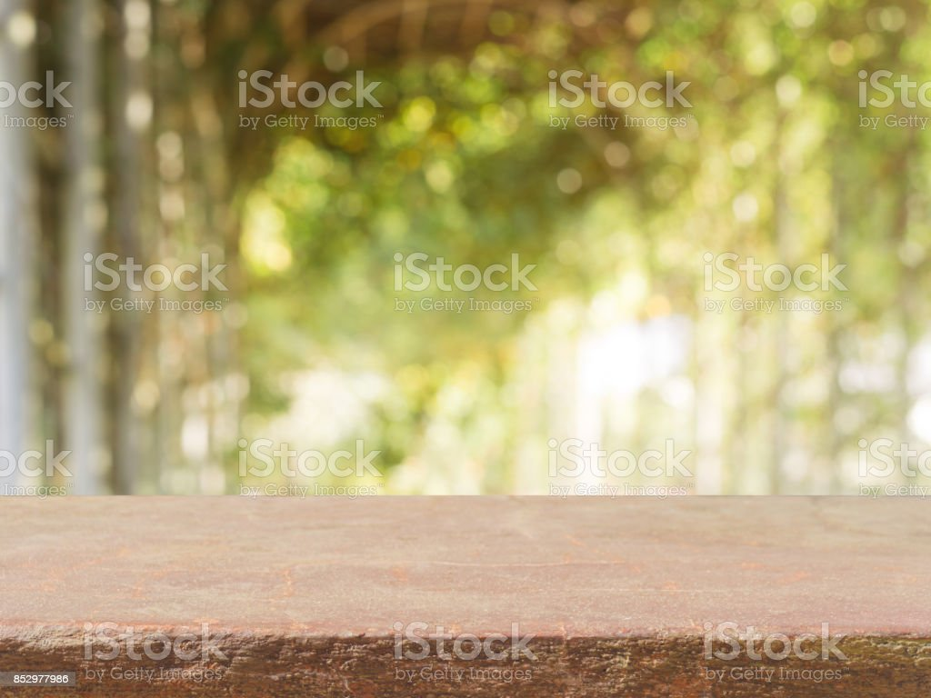 Stone board empty table top in front of blurred background. Perspective brown stone table top over blur trees in forest - can be used for display or montage your mock up products. spring season. stock photo