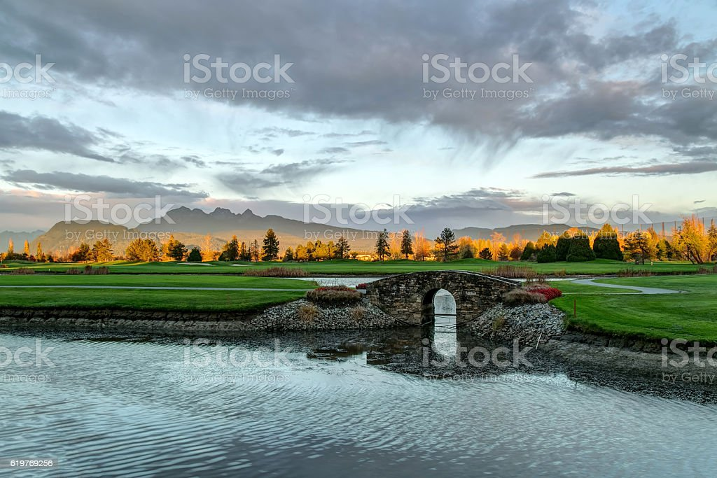Stone bridge over creek on golf course with autumn colors stock photo