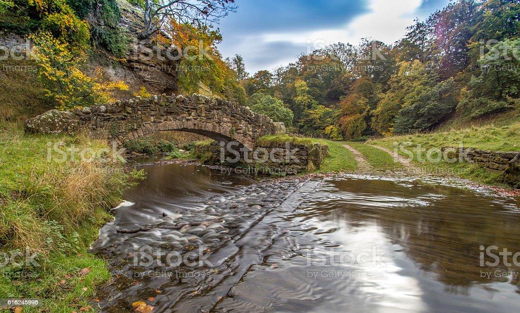 Stone Bridge over flowing stream stock photo