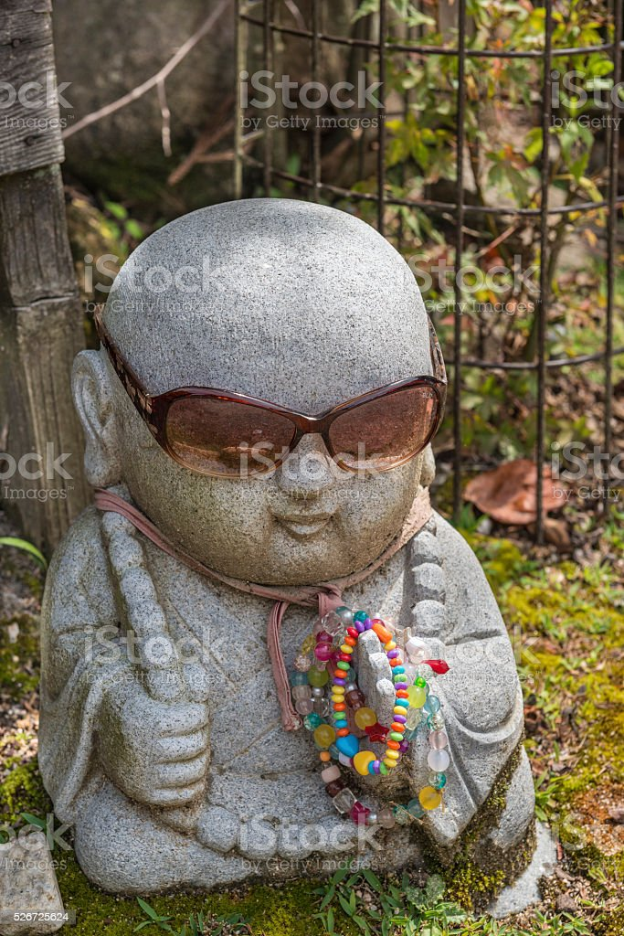 Stone Budha statue dressed up with shades and beads stock photo