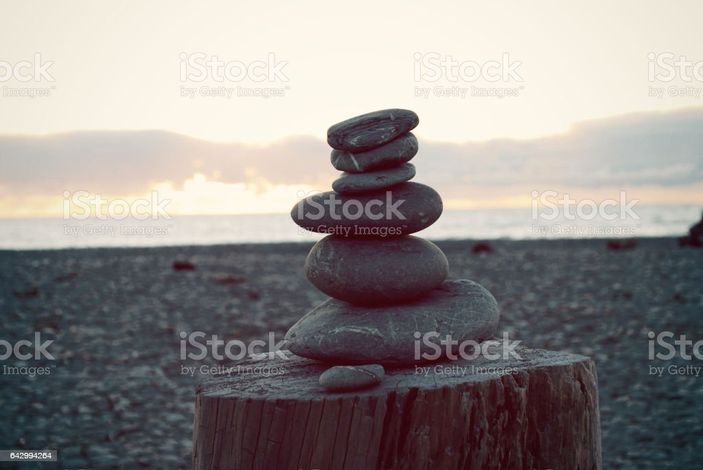 Stone Cairn Pile at Beach at Sunset stock photo