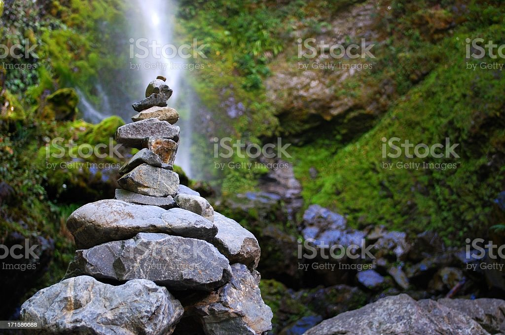Stone Cairn with distant Waterfall stock photo