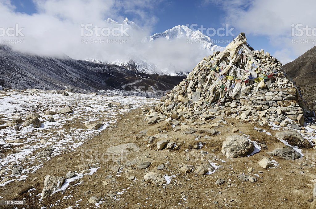 Stone cairn with tibetan flags marks sacred buddhist place,Nepal royalty-free stock photo