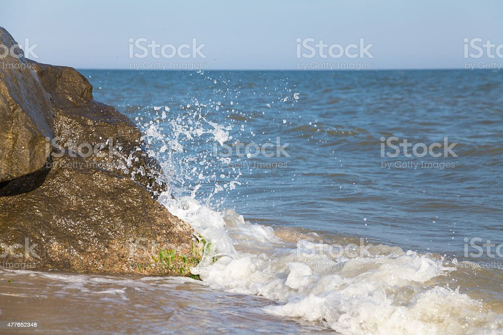 Stone cliff washed by sea wave stock photo