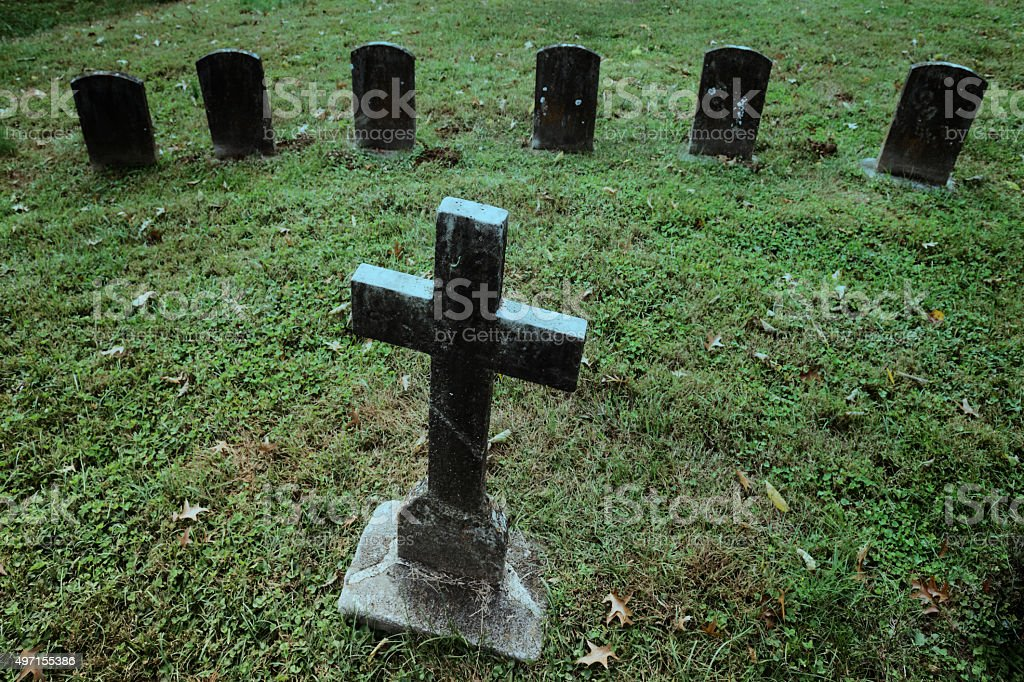 Stone cross at cemetery at dusk stock photo