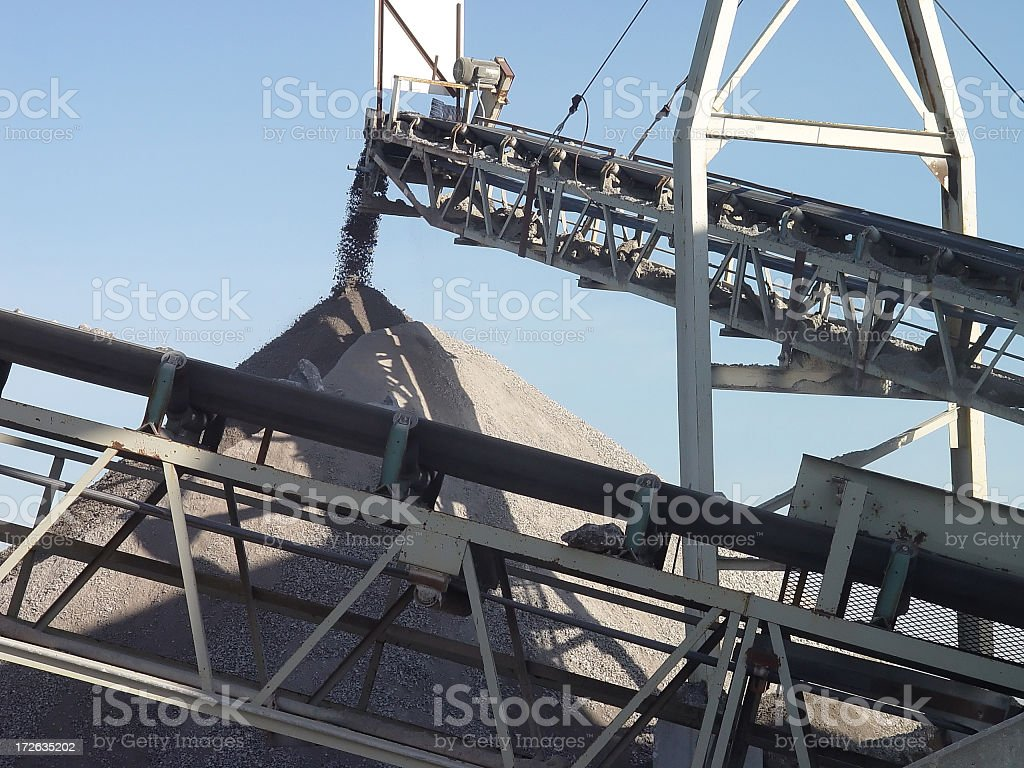 Stone crusher emptying out rocks onto a pile stock photo