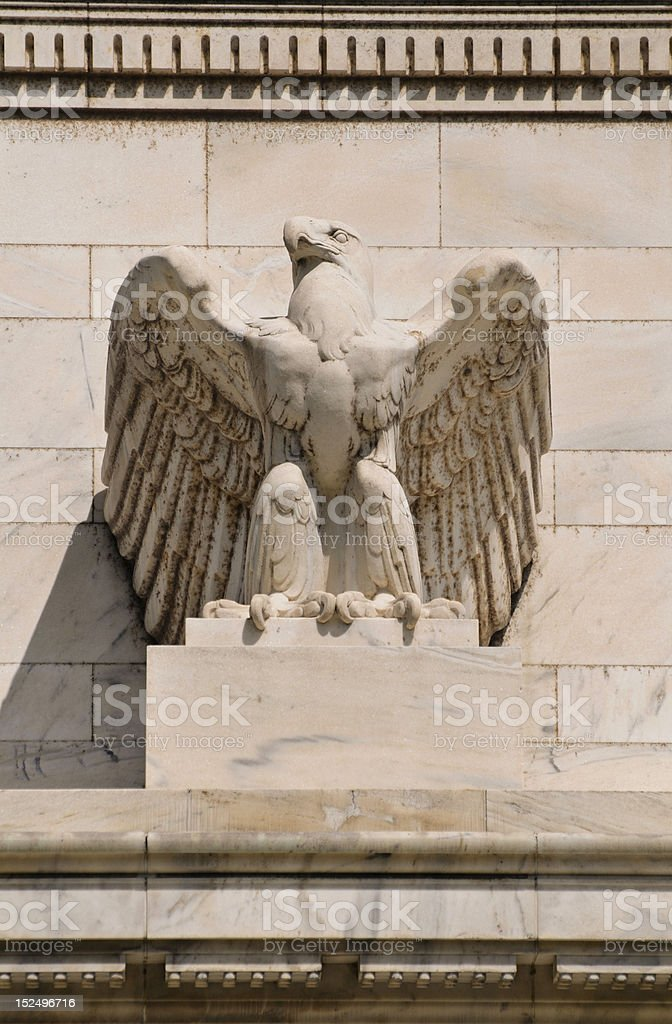 A stone eagle statue mounted on a building stock photo