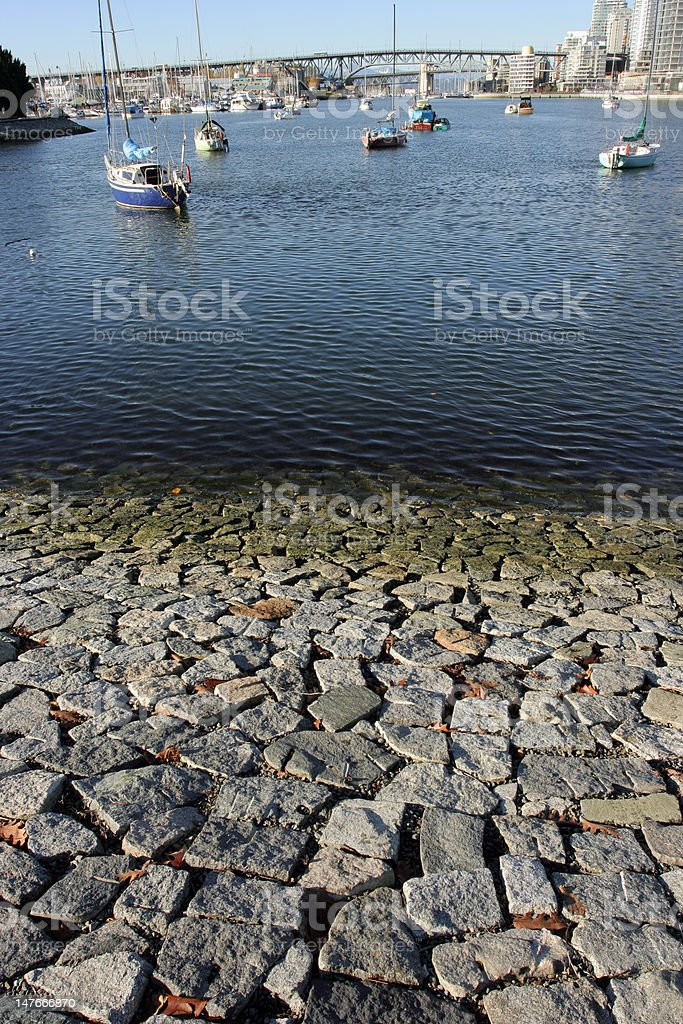 Stone emabankment with False Creek, Granville Bridge and anchored boats royalty-free stock photo