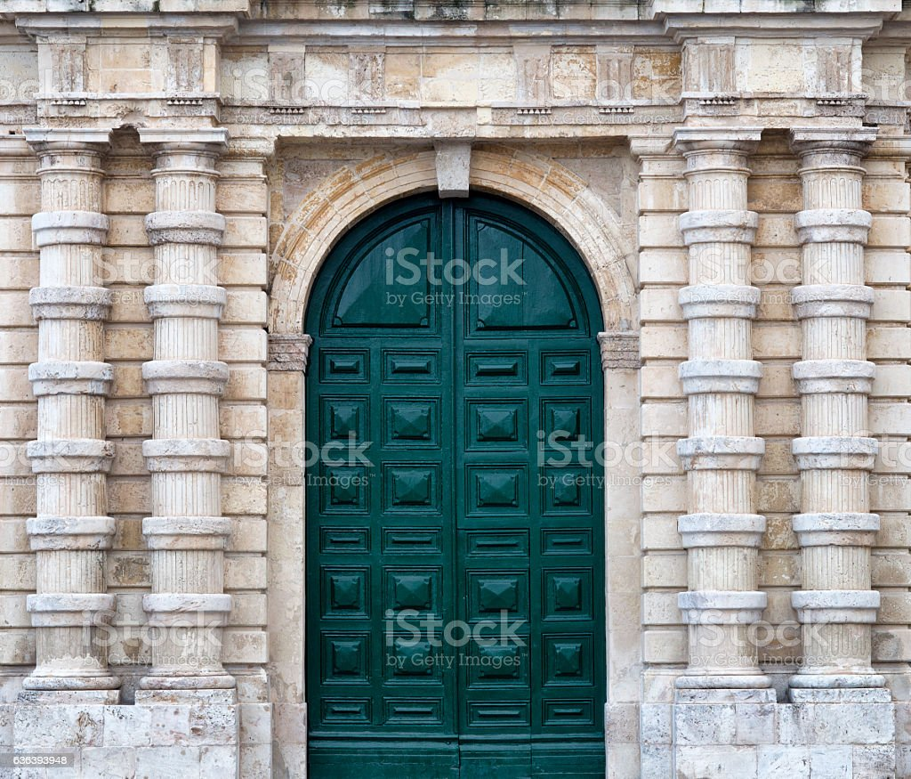 Stone facade with tall green wood door and decorative columns stock photo