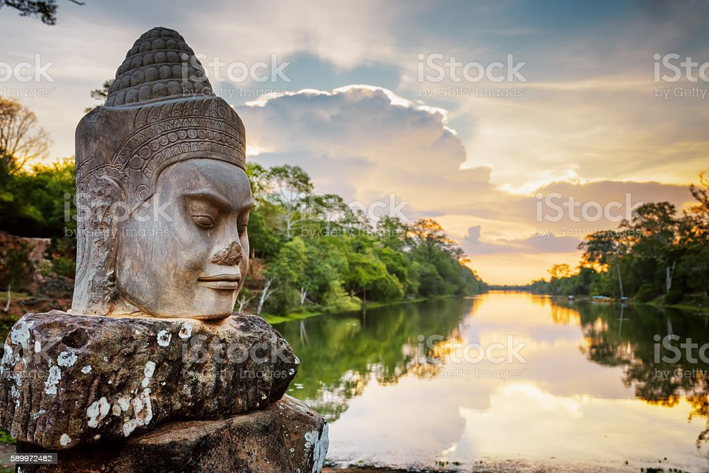 Stone face Asura and sunset over moat. Angkor Thom, Cambodia stock photo