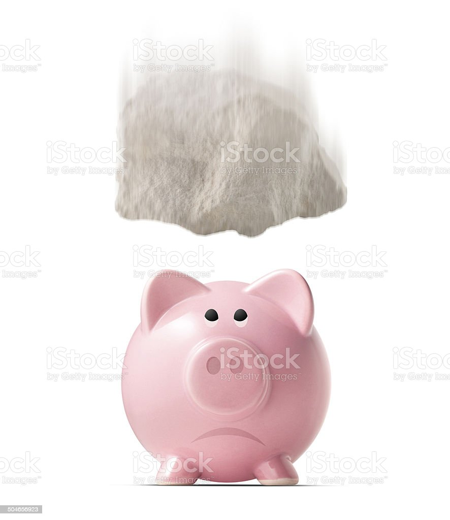Stone falling on piggy bank stock photo
