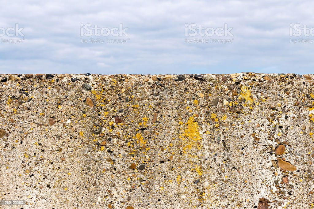 Stone (concrete) fence (block) close-up. Old and not smooth. On stock photo