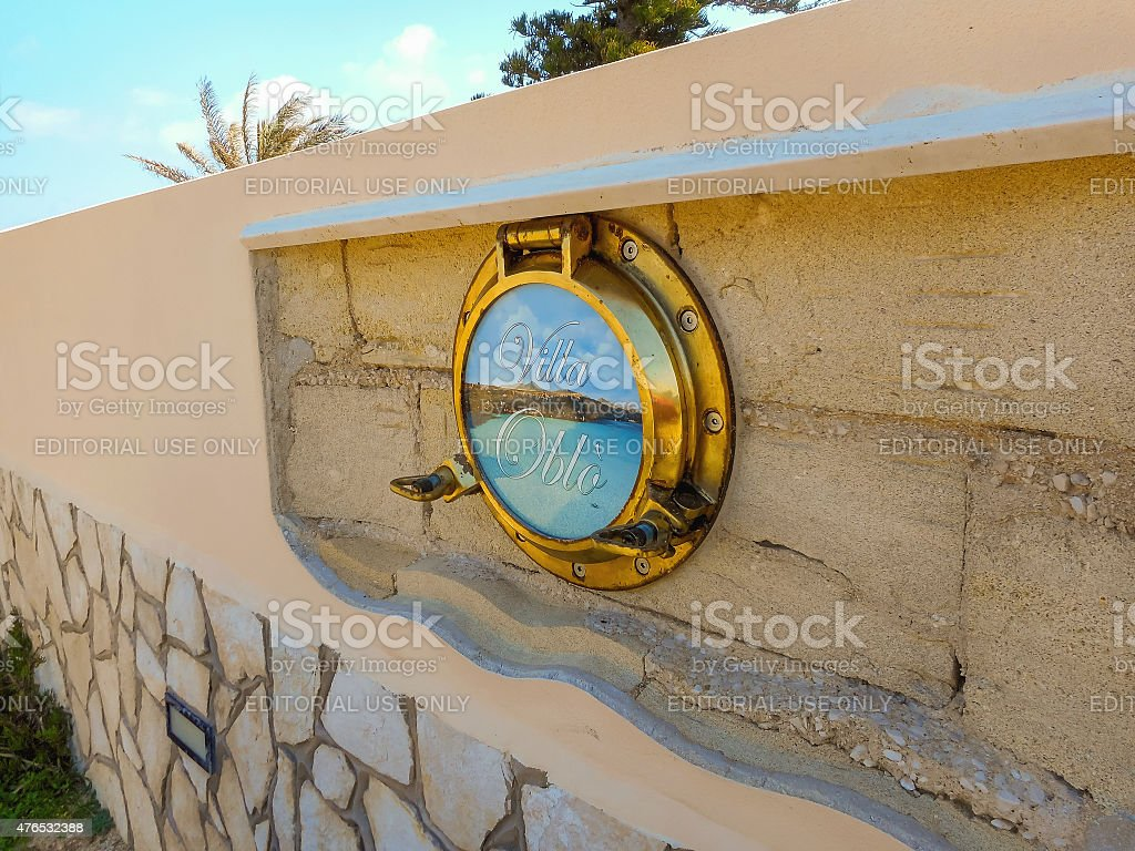 Stone fence of villa is decorated with the ship's porthole. stock photo