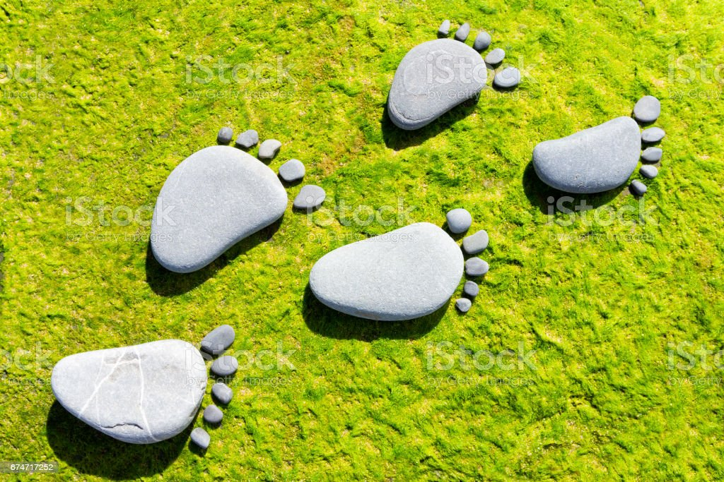 Stone footprints on green stock photo