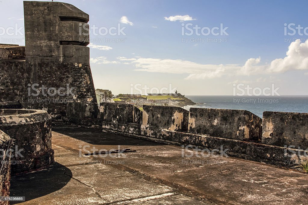 stone for wall overlooking the ocean and El Morro lighthouse stock photo