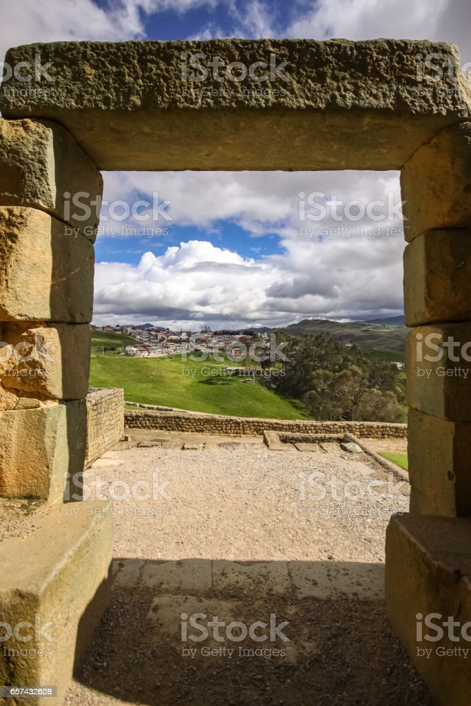 Stone gate at Ingapirca Inca ruins frames a view to green andean landscape stock photo